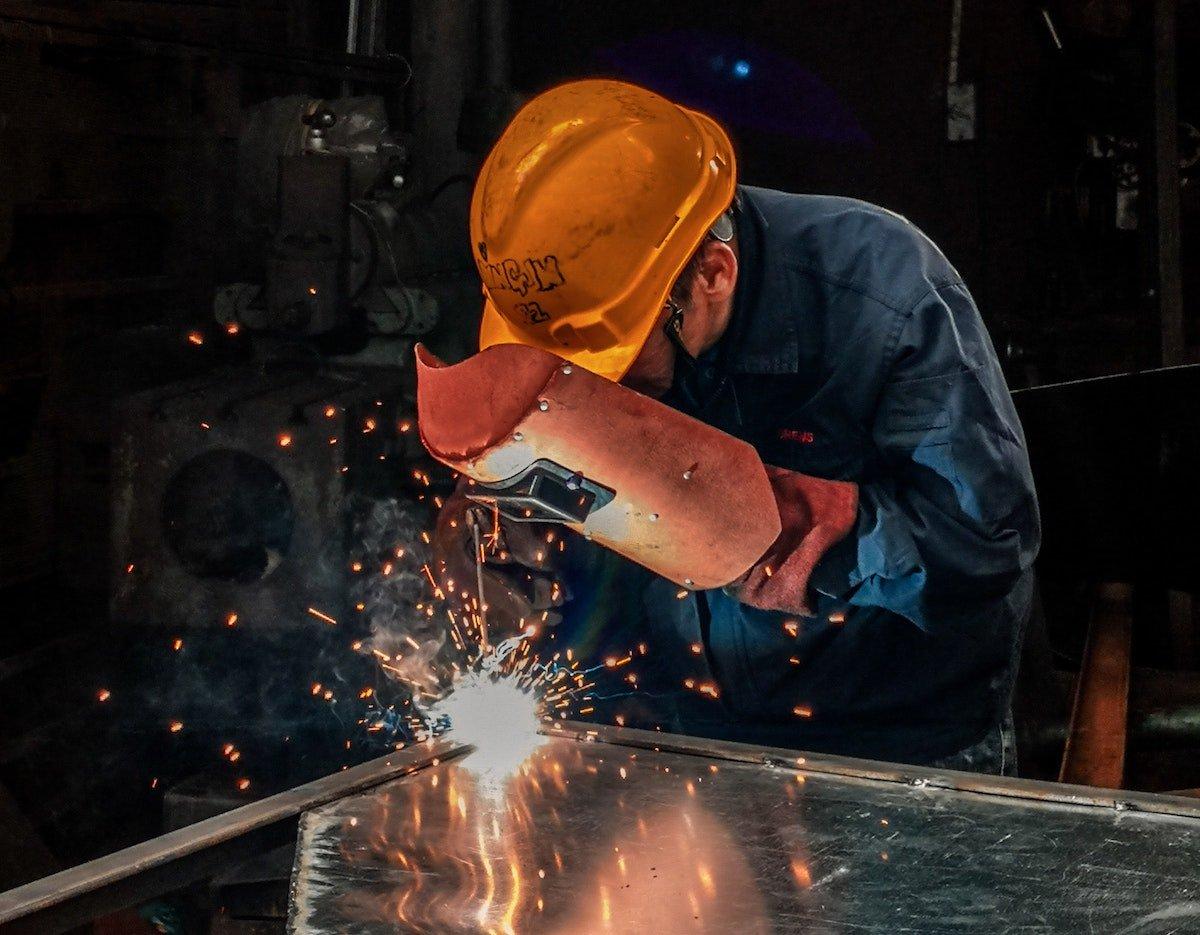 Hombre cortando placa de acero reciclado usando careta de protección